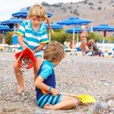 2 мальчика маленького ребенка играя на пляже с камнями Стоковое Фото