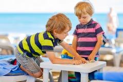 2 мальчика маленького ребенка играя на пляже с камнями Стоковая Фотография