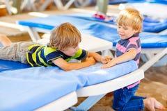 2 мальчика маленького ребенка играя на пляже с камнями Стоковые Фото