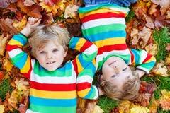 2 мальчика маленького ребенка кладя в листья осени в красочной одежде Стоковая Фотография