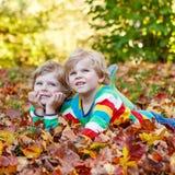 2 мальчика маленького ребенка кладя в листья осени в красочной одежде Стоковая Фотография RF