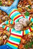 2 мальчика маленького ребенка кладя в листья осени в красочной одежде Стоковые Фотографии RF