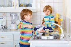2 мальчика маленького ребенка моя блюда в отечественной кухне Стоковая Фотография RF