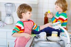 2 мальчика маленького ребенка моя блюда в отечественной кухне Стоковая Фотография