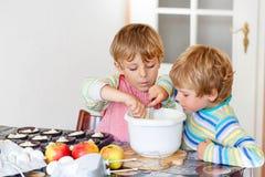 2 мальчика маленького ребенка печь торт яблока внутри помещения Стоковое Изображение