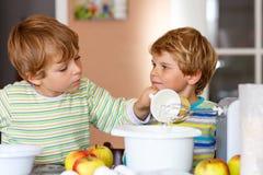 2 мальчика маленького ребенка печь торт яблока внутри помещения Стоковое фото RF