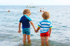 2 мальчика маленького ребенка принимая ванну в океане Стоковые Фотографии RF