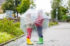 2 мальчика маленького ребенка с большим зонтиком outdoors Стоковые Изображения