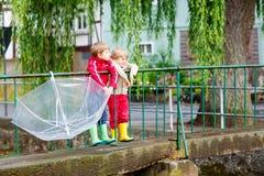 2 мальчика маленького ребенка с большим зонтиком outdoors Стоковые Фото