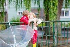 2 мальчика маленького ребенка с большим зонтиком outdoors Стоковая Фотография RF