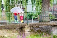 2 мальчика маленького ребенка с большим зонтиком outdoors Стоковое Изображение