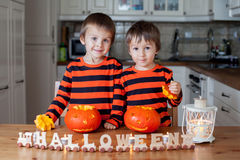 2 мальчика дома, подготавливающ тыквы на хеллоуин Стоковые Фото