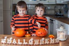 2 мальчика дома, подготавливающ тыквы на хеллоуин Стоковое Изображение