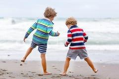 2 мальчика ребенк играя на пляже на бурный день Стоковое фото RF
