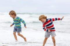 2 мальчика ребенк играя на пляже на бурный день Стоковые Изображения