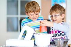 2 мальчика ребенк печь торт в отечественной кухне Стоковая Фотография