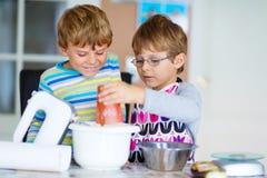 2 мальчика ребенк печь торт в отечественной кухне Стоковые Изображения