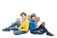 2 мальчика сидят на поле на стогах книг Стоковая Фотография RF