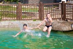 2 мальчика скачут в бассейн Стоковые Изображения