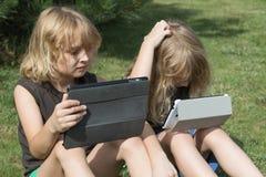2 мальчика с 2 таблетками сидят на лужайке Стоковое Изображение