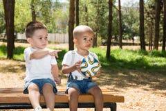 Мальчики: Афроамериканец и кавказец с футбольным мячом в парке на природе на лете Стоковая Фотография