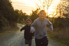 Мальчики бежать гонка на заходе солнца Стоковое Фото