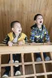 Мальчики взбираются деревянный усовик Стоковые Фото