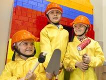 Мальчики в защитных шлемах с лопаткой, молотком и роликом Стоковые Изображения