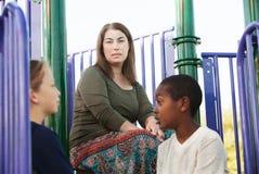 Мальчики женщины наблюдая говорят друг к другу Стоковые Изображения RF