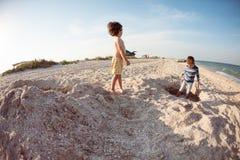 Мальчики играя с песком на пляже Стоковые Изображения