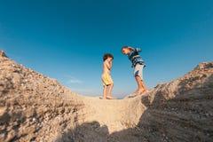 Мальчики играя с песком на пляже Стоковые Фото