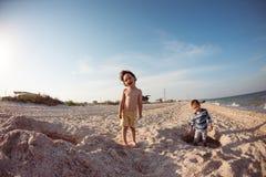 Мальчики играя с песком на пляже Стоковая Фотография