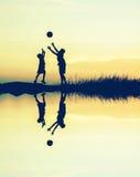 мальчики играя футбол на заходе солнца с отражением воды Silhouett Стоковое Фото