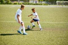 Мальчики играя футбол на поле Стоковые Изображения RF