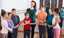 Мальчики и девушки изучая народный танец в студии Стоковые Изображения