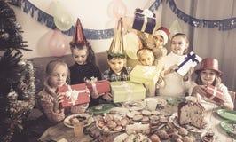 Мальчики и девушки обменивая подарки рождества Стоковые Изображения