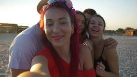 Мальчики и девушки принимая selfies на пляж на заходе солнца акции видеоматериалы