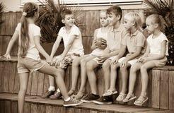 Мальчики и девушки сидя и играя с шариком outdoors Стоковые Изображения