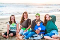 Мальчики и девушки сидя на песчаном пляже Стоковое фото RF
