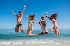 Мальчики и девушки скача на пляж Стоковая Фотография