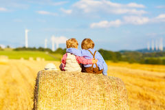2 мальчики и друз маленького ребенка сидя на стоге сена Стоковые Изображения