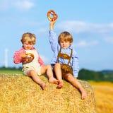 2 мальчики и друз маленького ребенка сидя на стоге сена Стоковые Фотографии RF