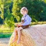 2 мальчики и друз маленького ребенка сидя на стоге сена Стоковые Изображения RF