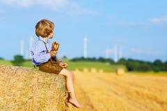 2 мальчики и друз маленького ребенка сидя на стоге сена Стоковые Фото