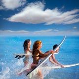 Мальчики и серферы девушек предназначенные для подростков бежать скакать на surfboards стоковые фото