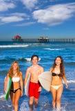 Мальчики и серферы девушек предназначенные для подростков приходя вне от пляжа стоковая фотография