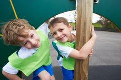 Мальчики на взбираясь стене в классе физкультуры школы Стоковая Фотография
