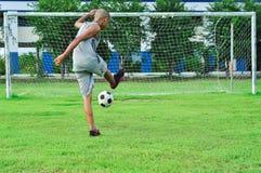 Мальчики ребенка молодые пиная футбольный мяч оягнитесь играть футбол Стоковые Фотографии RF