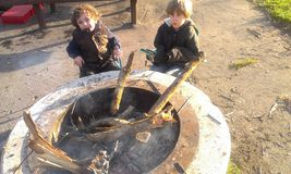 Мальчики сидя вокруг ямы огня лагеря Стоковые Фотографии RF