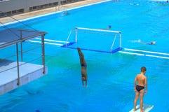 Мальчики скача в открытый бассейн Стоковые Фото
